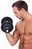 Bare-chested and muscular man doing fitness with dumbbell — Stock Photo