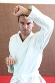 Man wearing martial arts clothing stood in defence stance — Stock Photo