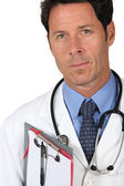 Male doctor stood with clipboard — Stock Photo