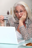 Elderly lady confused by prospect of shopping on line — Stock Photo