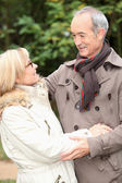 Older couple embracing on a winter's stroll — Stock Photo