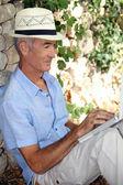 Senior man using a laptop in the sunshine — Stock Photo