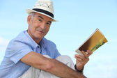 Carefree man reading a book outside — Stock Photo