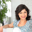 Стоковое фото: Womin flowery top sitting on sofa