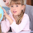 Little girl and mother looking at globe — Stock Photo