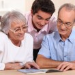 Couple of senior citizens having their grandson home — Stock Photo