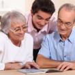 Couple of senior citizens having their grandson home — Stock Photo