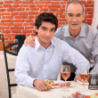 Two generations sitting in a restaurant - Stock Photo