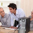 Elderly couple in front of a computer — Stock Photo