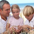 Young family at the beach — Stock Photo