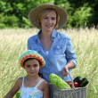 Mother and daughter carrying baskets full of vegetables - Foto Stock