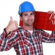 Handyman carrying tool box on shoulder and giving the go-ahead - Photo