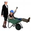 Architect pushing her colleague in wheelbarrow — Stock Photo