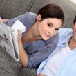 Couple reading a newspaper at home — Stock Photo