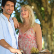 Couple with a bike and basket of produce — Stock Photo #8677223