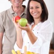 Man and woman with a basket of fresh fruit - Stock Photo
