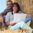 Couple relaxing with laptop in straw — Stock Photo