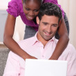 Black woman leaning on his boyfriend and doing computer laid on his boyfri — Stock Photo #8677418