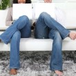 Mirror image of a couple in jeans using white laptops on a white sofa — Stock Photo #8678442