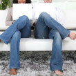 Mirror image of couple in jeans using white laptops on white sofa — Stock Photo #8678442