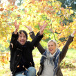 Couple throwing leaves in air — Stock Photo #8678920