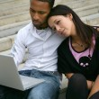 Young couple on some steps with a laptop - Stock Photo