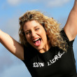 Excited blond stood outdoors with arms in the air - Stock Photo
