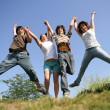 Four teenagers jumping — Stock Photo