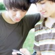 Two male teens reading text message — Stock Photo