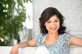 Kobieta w kwieciste góry siedząc na kanapie — Zdjęcie stockowe