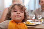Cute toddler having dinner with parents — Stock Photo