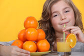 Little girl drinking freshly squeezed orange juice — Stock Photo