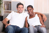 Mixed race couple sat on couch — Stock Photo