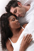 Interracial couple sleeping — Stock Photo