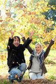 Couple throwing leaves in the air — Stok fotoğraf