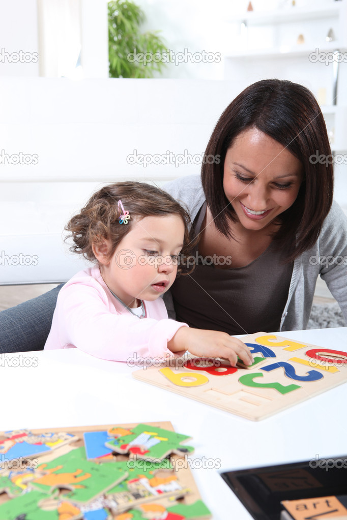 Mother and young daughter doing jigsaw puzzles — Stock Photo #8672122