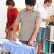 Stok fotoğraf: Men housemates doing daily chores