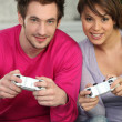 Stock Photo: Young couple playing a games console