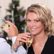 Pretty young woman drinking champagne with her boyfriend at Christmas — Stock Photo