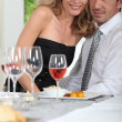 Woman sitting on her partner's lap at the dinner table — Stockfoto #8688338