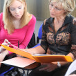 Two women discussing work in a folder — Stock Photo #8688501