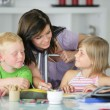 Mother watching brother and sister doing their homework — Stock Photo