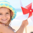 Little girl playing with wind toy on beach — Stock Photo #8688667