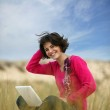 Brunette using laptop at the beach — Stock Photo