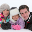 Stock Photo: Young family lying in the snow