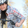 Young woman pushing a bicycle and wearing a helmet — Stock Photo #8689585