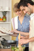 Woman and man smiling cooking using cookbook — Stock Photo