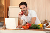 Man in kitchen with laptop and vegetables — Stock Photo