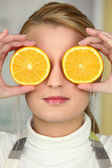 Young woman using orange halves as eyes — Stock Photo