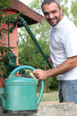 A mid aged man filling a watering can with a cast iron water pump — Stock Photo